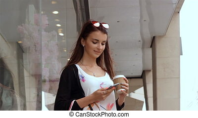 young cute brunette with purchases worth on the street and tolls for telephone