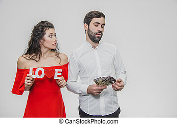 Young cute couple in love. A man holds money in his hands, a woman with a wooden word of love. Isolated on a white background. Valentine's Day