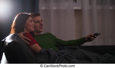 Young cute couple lying on the couch and watching TV