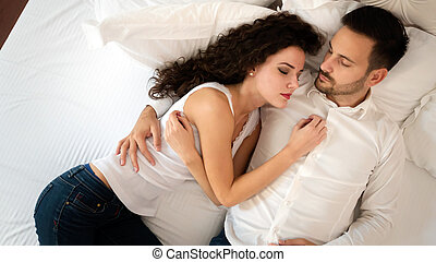 Young cute couple lying together on bed