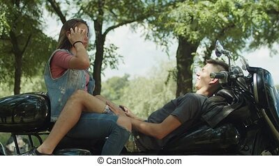 Young cute couple travelers relaixing on motorbike -...