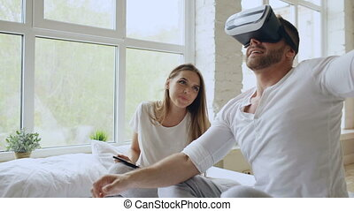 Young cute couple with tablet computer and virtual reality headset playing 360 VR video game while sitting in bed at home