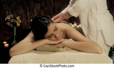 Young cute female model looking camera getting back massage...