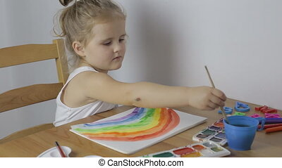 Young cute girl draws a rainbow