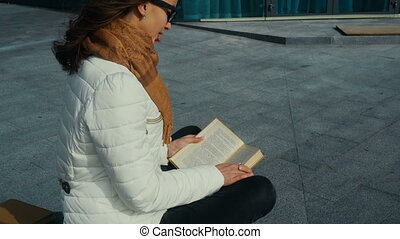 young cute girl in glasses reading a book in the street