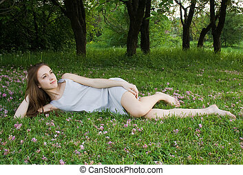 Young cute girl is leaning on the green gras