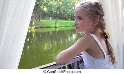 young cute girl looking through window during boat trip