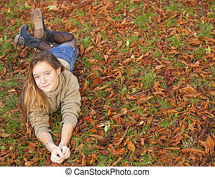 Young cute girl lying on the fallen yellow leaves in autumn park.