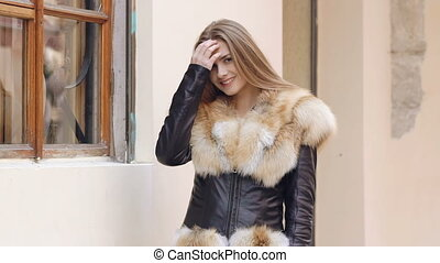 Young cute girl posing in furry jacket on the street. Slow motion