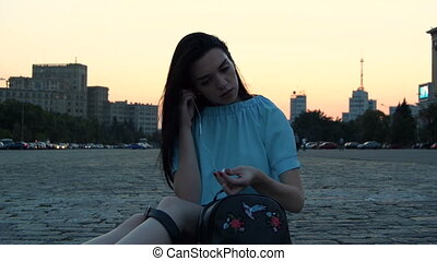 young cute girl sitting on the street in the evening and inserts in-ear headphones
