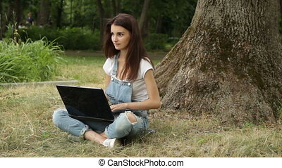 young cute girl with great laptop sitting in the summer on the grass