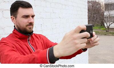 Young cute guy doing selfie near white brick wall