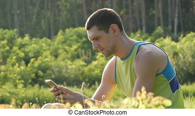 Young cute man looking at smartphone on green grass against...