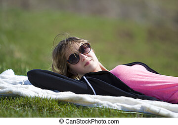 Young cute pretty blond girl in black sweater and dark sunglasses lies on white towel on green grass enjoying nature and warm sunny day smiling happily in camera.