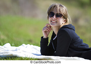 Young cute pretty blond girl in black sweater and dark sunglasses lies on white towel on green grass enjoying nature and warm sunny day smiling happily in camera showing wonderful white teeth.