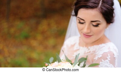 Young cute smiling bride with blue eyes holding a bouquet of flowers in her hands.