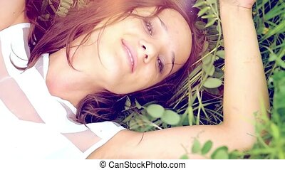 young cute summer brunette girl  lays down in  flower meadow  and smelling the flowers thoughtfully romantic, relaxing smiling