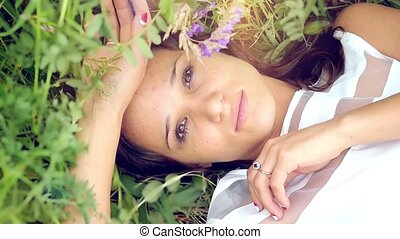 young cute summer brunette girl lying on a flower meadow relaxing smiling and smelling the flowers thoughtfully