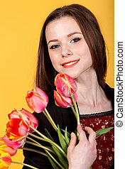 Young cute teen brunette girl with tulips