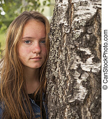 Young cute teen girl with long hair portrait near the tree.