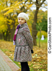 young cute teenager girl in white beret and color scarf in autumn beautiful park