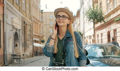 Young cute tourist is talking on the phone outside, wearing hat, glasses