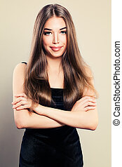Young Cute Woman in Black Dress. Smiling Girl with Crossed Arms