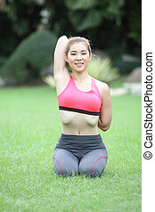 Young cute woman in cow face yoga pose on lawn