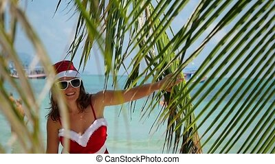 Young cute woman in santa hat look out from palm tree of branch on tropical beach in slow motion. 1920x1080