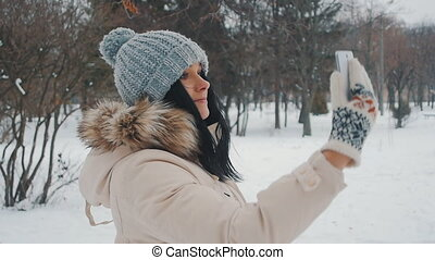 Young cute woman in winter park doing selfie with her smartphone