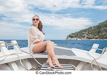 Young cute woman posing on a yacht