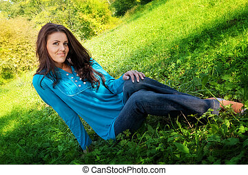 Young cute woman resting on green fresh grass