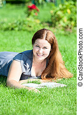 Young cute woman with an open book resting on green lawn