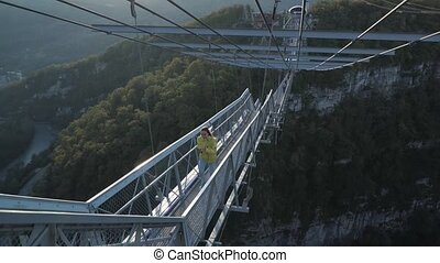 Young cutie run through modern cable bridge. Happy mood on autumn vacation. Adventuring on huge bridge. Golden hour in the marvelous autumn canyon.
