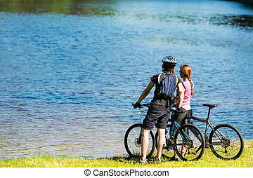 Young cyclist couple watching the lake