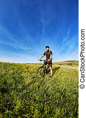 Young cyclist cycling on the green meadow against beautiful blue sky with clouds in the countryside.