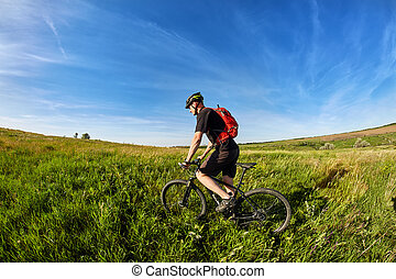 Young cyclist riding mountain bicyclist against beautiful sunrise in the countryside.