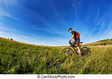 Young cyclist riding mountain bicyclist against beautiful sunset in the countryside.
