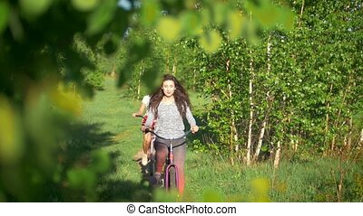 Young cyclists on a summer walk passing by the bushes and...