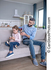 Young dad and little daughter sitting on the sofa at home.