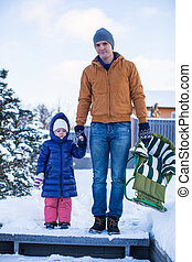 Young dad and little girl go sledding in a cold winter day