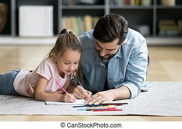 Young dad have fun drawing with little daughter
