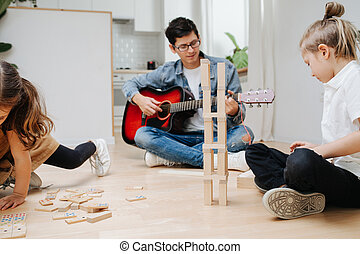 Young dad playing guitar, watching children playing with wooden blocks.