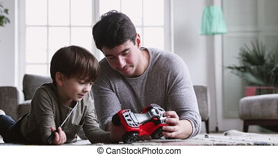 Young dad teaching preschool son play toy car at home