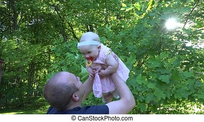 Young daddy lift his happy baby daughter near tree in park....