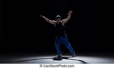 Young dancer man dancing breakdance on black