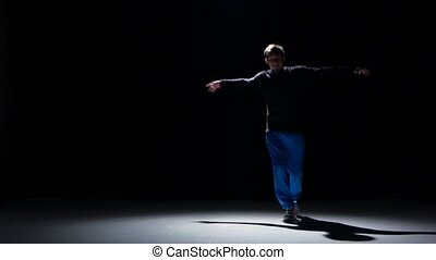 Young dancer man goes on dancing breakdance, black