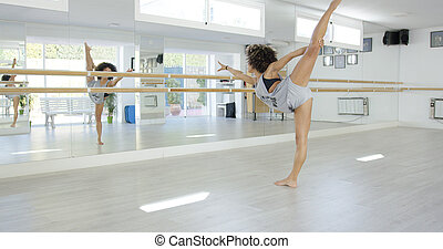 Young dancer practising in a dance studio - Young barefoot...