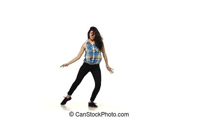 Young dancing lady style brunette woman in plaid shirt on white background, slow motion