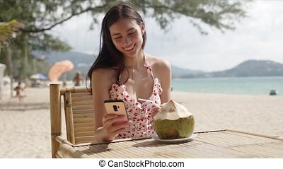 Young dark haired female in casual summer dress checking message on smartphone while sitting in beach cafe and refreshing with coconut water